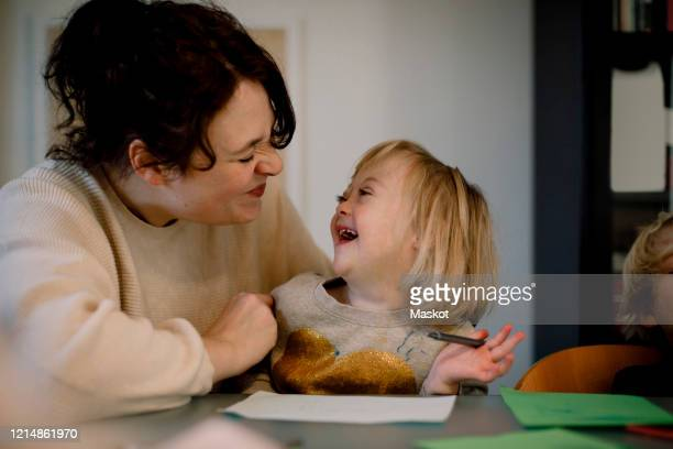 mother making facial expressions while playing with disabled daughter at dining table - disability stock pictures, royalty-free photos & images