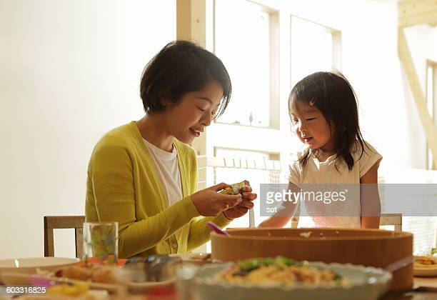 Mother making Hand Roll Sushi with little girl