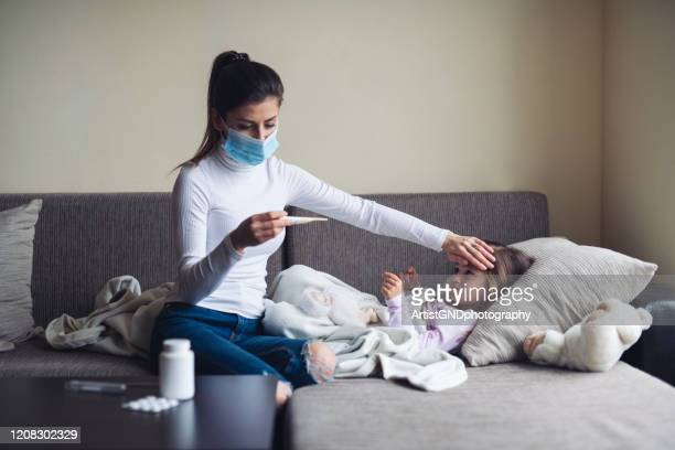 a mother measure temperature on her sick child at home. - illness stock pictures, royalty-free photos & images