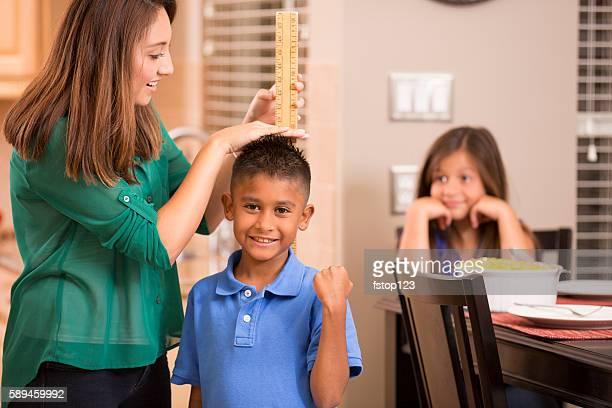 mother measures growing son's height with yard stick. - lang lengte stockfoto's en -beelden