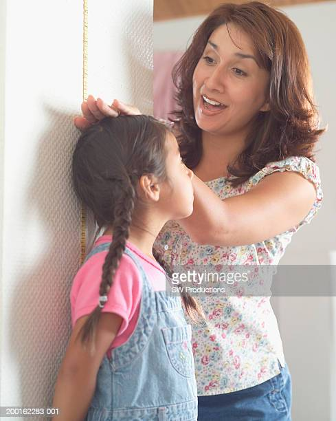 Mother measuring daughter's (3-5) height against wall