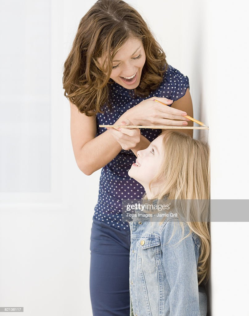 Mother measuring daughter?s height : Stock Photo
