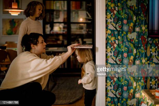 mother measuring height of disabled daughter with book on wall - disabilitycollection stock-fotos und bilder