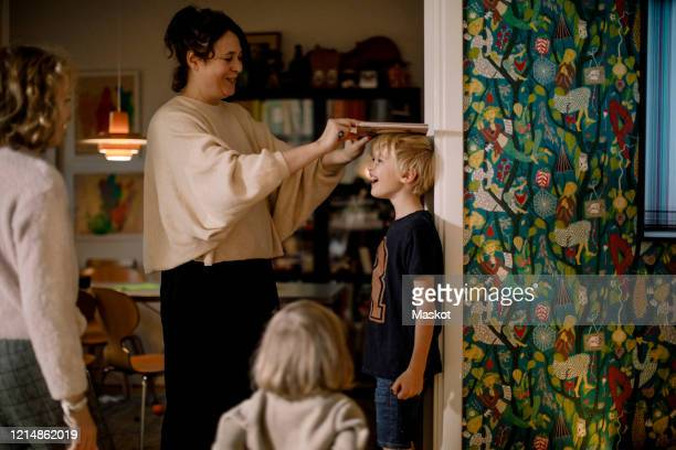 mother measuring height of smiling son with book on wall - instrument of measurement stock pictures, royalty-free photos & images