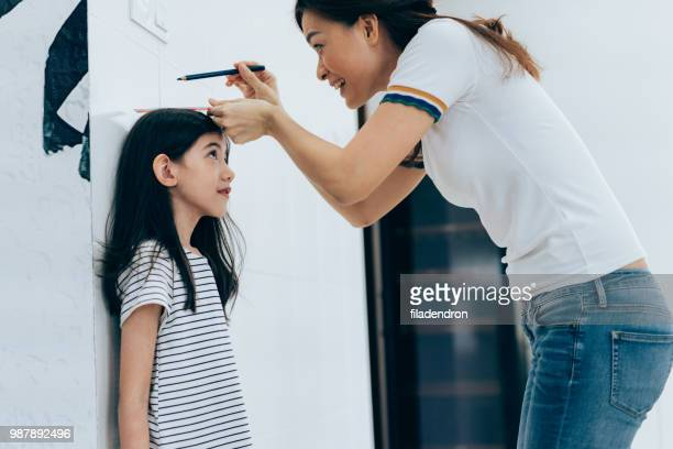 Mother measuring her daughter's height