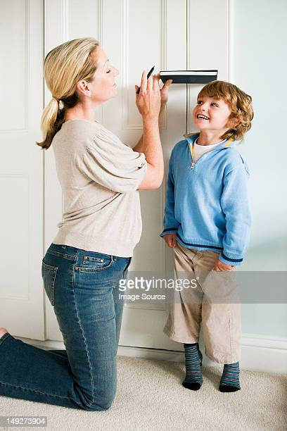 mother measuring her son against a door with a book - つま先 ストックフォトと画像