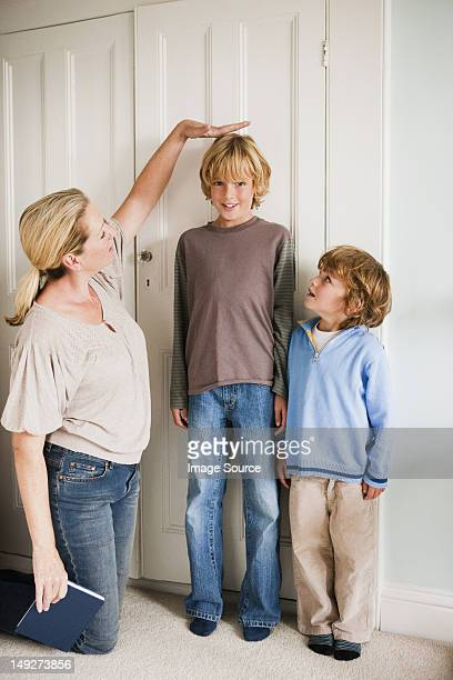Mother measuring her sons at home