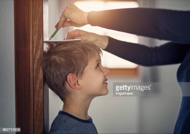 mother measuring son's height - high up stock photos and pictures