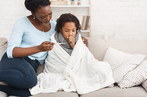 Mother measuring temperature of her sick daughter with thermometer 1187580897