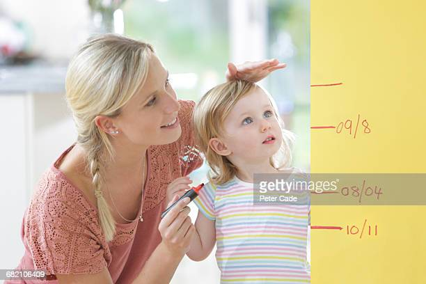 mother measuring toddler daughter against wall - felt tip pen stock pictures, royalty-free photos & images