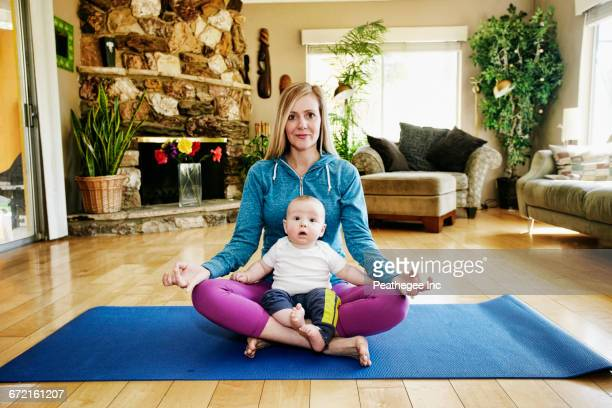 mother meditating on exercise mat with baby in lap - mom sits on sons lap stock pictures, royalty-free photos & images