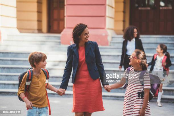 mother meeting kids after first day at school - working mother stock pictures, royalty-free photos & images