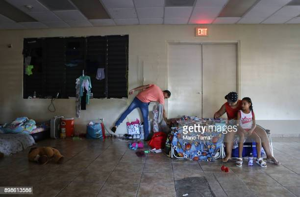 Mother Midiam Rivera fixes daughter Janellise's hair as stepfather Jesus M Montijo reaches into a bag in a shelter for Hurricane Maria victims on...