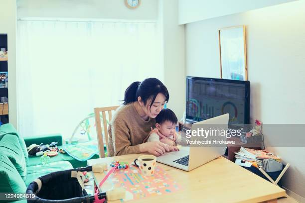mother multi-tasking with infant daughter in home kitchen - テレビ会議 ストックフォトと画像