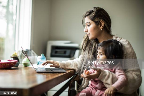 mother multi-tasking with infant daughter in home office - mother photos et images de collection