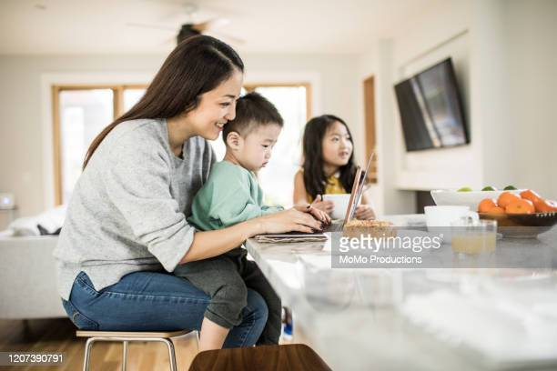 mother multi-tasking with young children in kitchen table - korean ethnicity stock pictures, royalty-free photos & images