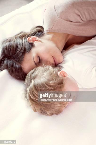 mother napping with young son - abbracciarsi a letto foto e immagini stock
