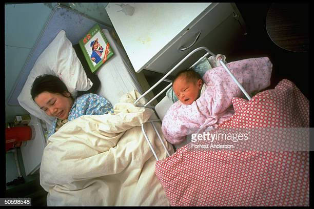 Mother newborn in bed crib at Beijing No 6 Hospital re proposed eugenics law aimed at diseased retarded to improve quality of population