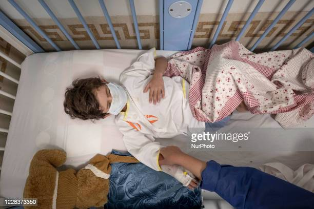 Mother of 7yearold boy Mohammad Amin cares of her son who is infected by the new coronavirus disease and wearing a protective face mask as he lies on...