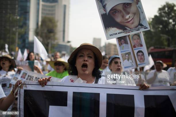 A mother of a disappeared chants and holds up a sign with the image of her missing son during a march on Mother's Day on May 10 2017 in Mexico City...