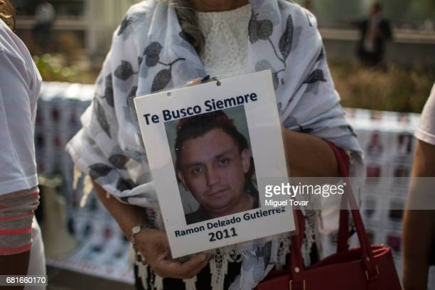 A mother of a disappeared holds a sign with the image of her missing son during a march on Mother's Day on May 10 2017 in Mexico City Mexico Mothers...