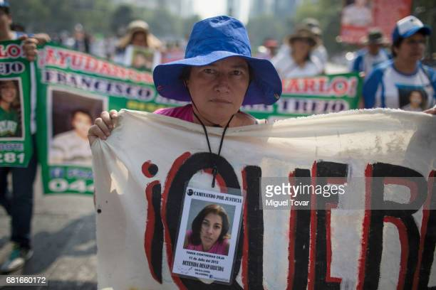 A mother of a disappeared holds up signs with images of her missing relative during a march on Mother's Day on May 10 2017 in Mexico City Mexico...