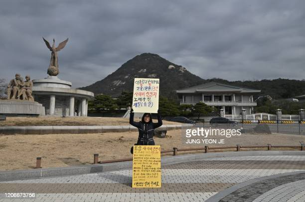 A mother of a Shincheonji Church of Jesus follower holds a placard reading President please save my daughter who became a slave to Shincheonji during...