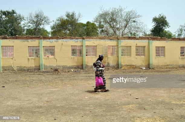 A mother of an abducted Chibok girl walks on April 14 2015 past the school hostel where 219 schoolgirls by Boko Haram Islamists the girls were...