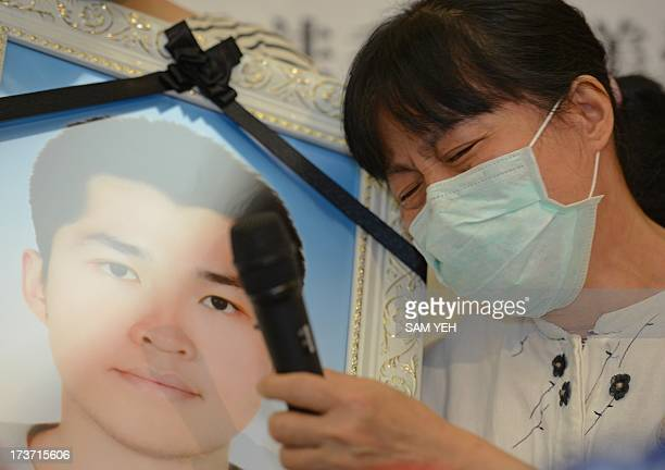 Mother of Hung Chungchiu speaks next to his portrait during a press conference at parliament in Taipei on July 17 2013 after Hung was found by a...