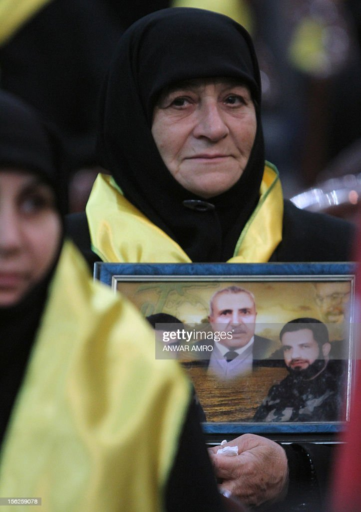 A Mother of killed Hezbollah fighter watches Hezbollah chief Hassan Nasrallah speak during a televised address to a rally marking the party's Martyrs' Day in southern Beirut, on November 12, 2012.