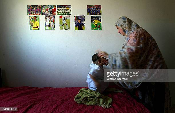 Mother of Leith Fuad Mosa age 3 dresses him a white dishdasha before he is circumcised on June 29 2007 in Baghdad Iraq Circumcision the procedure...