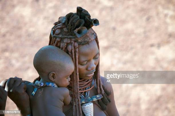 mother of the himba tribe with her baby in the town of purros, kaokoland, namibia - himba photos et images de collection