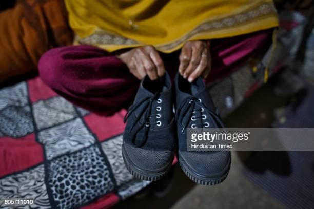 Mother of the rapemurder victim holds the shoes of her daughter at her home at Jhansa village on January 16 2018 in Jind India A Class 12 student is...