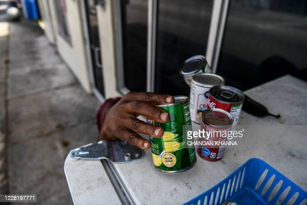 Mother of three children Avis Alexander 55, takes free food from a community refrigerator in Miami, Florida on August 25, 2020. - Sherina Jones a...