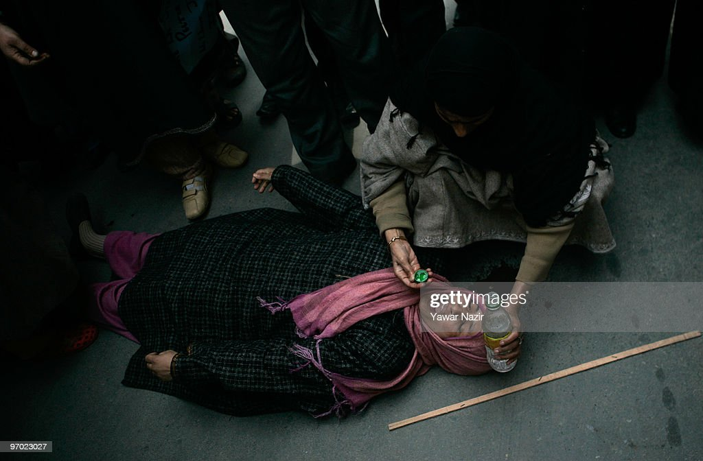 Mother of Wamiq Farooq, a 13-year-old teenager who was killed by a teargas shell fired by Indian police last month, faints on ground during a protesting against Indian police on February 24, 2010 in Srinagar, the summer capital of Indian administered Kashmir, India. The family were protesting against an Indian police report on that described Wamiq Farooq, 13, who was killed by a police teargas canister on January 31, as a 'miscreant' and as part of an unlawful assembly. The family deny the police report and accuse the Indian police of killing their son. They say Wamiq was playing cricket when an Indian police officer fired a teargas shell which hit his head.