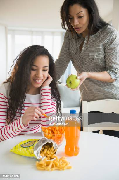 Mother offering daughter healthy snack