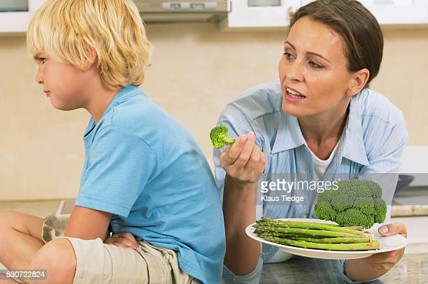 Mother offering her son vegetables