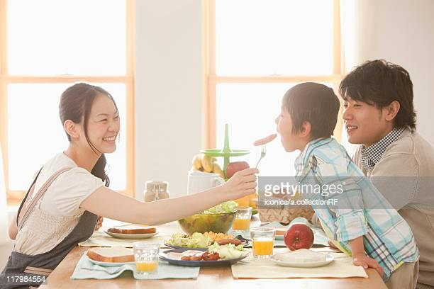 Mother Offering Sausage to Son, Father Watching