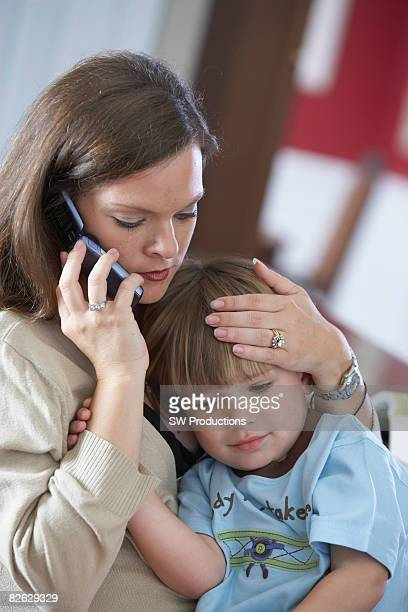 Mother on phone holding sick son