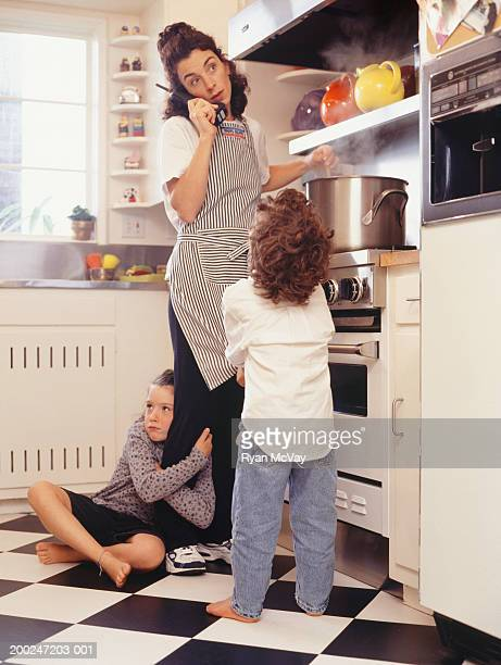 Mother on phone, two children (4-5) (6-7) seeking attention in kitchen