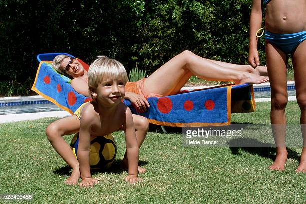 mother on sun lounger, two children in foreground - bikini bottom stock pictures, royalty-free photos & images