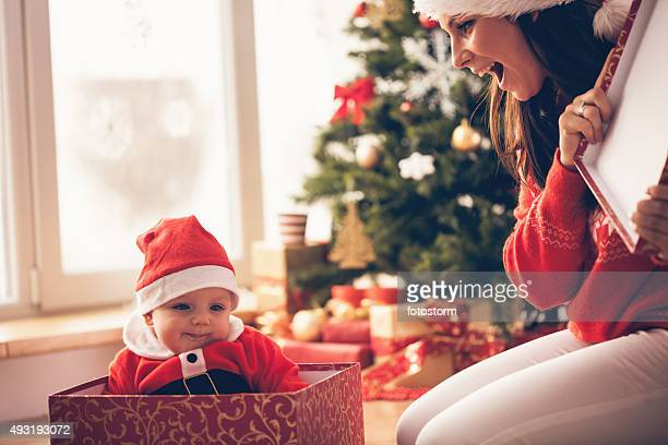 Mother opening Christmas present with baby inside