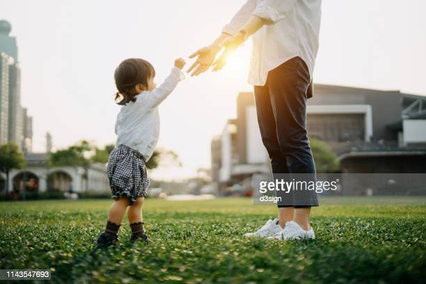 mother opening her arms out as daughter approaches in the park at sunset - miembro parte del cuerpo fotografías e imágenes de stock