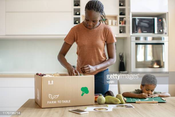 mother opening parcel with meal kit and her son drawing with chalk - grocery delivery stock pictures, royalty-free photos & images