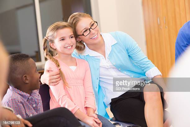 Mother or teacher hugging young girl in group meeting