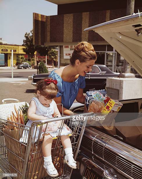 A mother out shopping with her young daughter loads the groceries into the car circa 1960