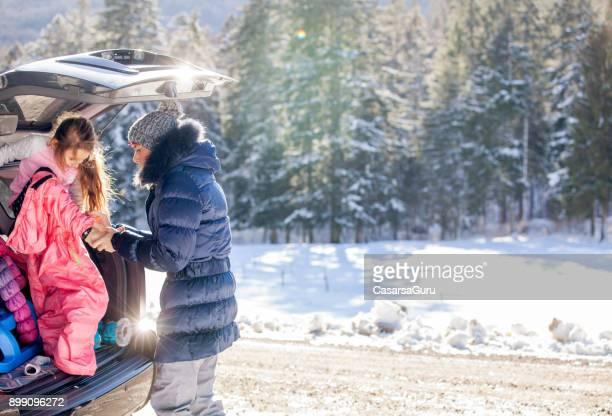 Mutter Natur auf dem Schnee hilft Tochter immer Kleid In warme Winterkleidung