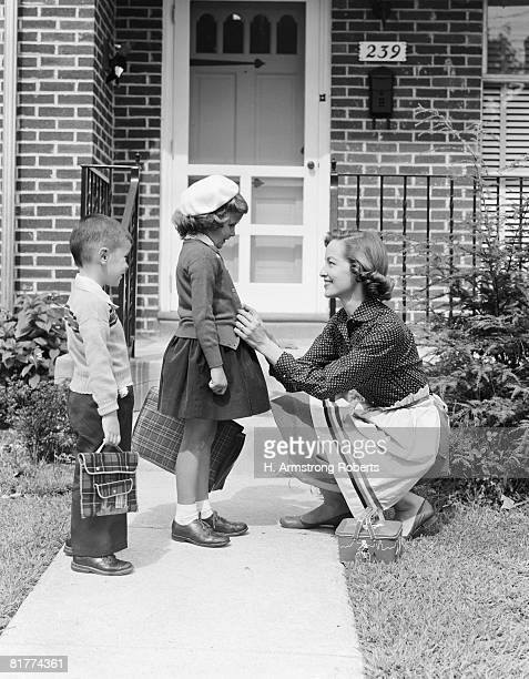 mother outside front door, buttoning sweater of daughter going off to school with her brother. (photo by h. armstrong roberts/retrofile/getty images) - bambini scuola bianco e nero foto e immagini stock
