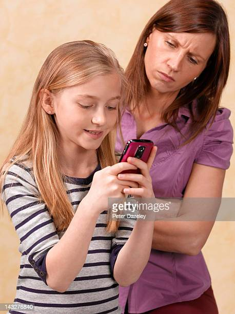 mother overseeing 10 year old girl texting - sad 10 year girl stock photos and pictures