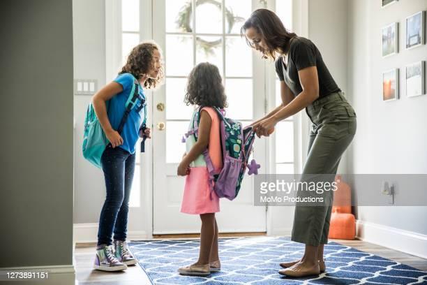mother packing daughters backpacks for school - preparation bildbanksfoton och bilder